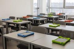 Modern klaslokaalbinnenland, met het werkbureaus en stoelen; stadsmening op de achtergrond Stock Afbeeldingen