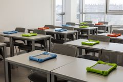 Modern klassruminre, med arbetsskrivbord och stolar; stadssikt i bakgrunden Arkivbilder