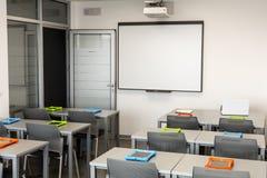Modern klassruminre, med det vita brädet, arbetsskrivbord och stolar Arkivbild