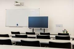 Modern klassruminre, med det vita brädet, arbetsskrivbord och stolar Fotografering för Bildbyråer