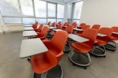 Modern klassruminre, med det vita brädet och movabletabeller och stolar Teaterstilinställning Royaltyfri Foto