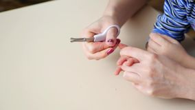 Modern klipper av barnet som ` s spikar med sax Mammatillvaratog händerna av hennes barn Närbild lager videofilmer