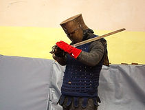 Modern knight. Knight in armor in red gloves holding a sword in training Royalty Free Stock Photography