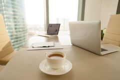 Modern kontorsarbetsplats, kaffekopp, bärbara datorer på konferensnegot Royaltyfri Bild