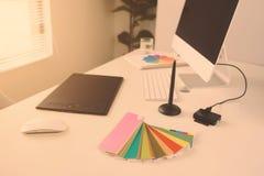 Modern kontorsarbetsplats med den skrivbords- datoren, nålen och minnestavlan Royaltyfri Foto