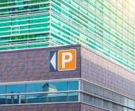 Modern kontorsbyggnad med parkeringspekareeftermiddag Royaltyfri Bild