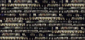 Modern kontorsbyggnadfasad, folk som arbetar på natten royaltyfria bilder