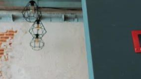 Modern kontorsinre med den gamla tappningtegelstenväggen en verklig modern inre i vindstil Vänd på den ljusa kulan, ljus stock video