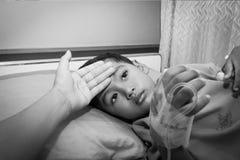 Modern kontrollerade för feber hennes sjuka son, medan vila arkivfoton