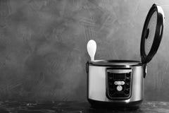 Modern krachtig multikooktoestel op lijst tegen grijze achtergrond stock fotografie