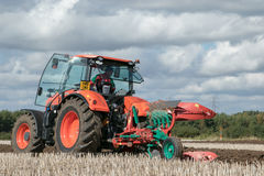 Modern Kubota tractor pulling a plough Royalty Free Stock Images