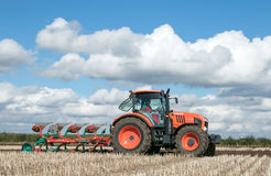 Modern Kubota tractor pulling a plough Stock Photos