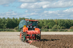 Modern Kubota tractor pulling a plough Stock Photography