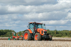 Modern Kubota tractor pulling a plough. Orange modern Kubota M7151  tractor ploughing a field with plough working field at ploughing match Royalty Free Stock Photography