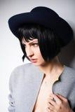 Modern kvinna med den svarta hatten på grå färger Royaltyfria Foton