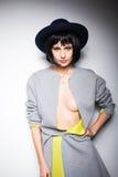 Modern kvinna med den svarta hatten på grå färger Fotografering för Bildbyråer