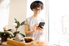 Modern kvinna som använder smartphonen i kafé arkivfoton