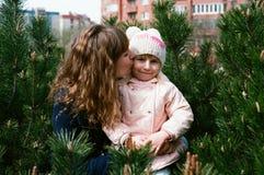 Modern kysser dottern i en kind försiktigt Arkivbild