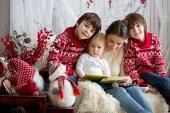 Modern läser boken till hennes söner, barn som sitter i hemtrevlig fåtölj på en snöig vinterdag royaltyfri fotografi