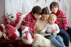 Modern läser boken till hennes söner, barn som sitter i hemtrevlig fåtölj på en snöig vinterdag royaltyfri foto