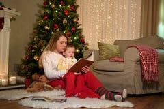 Modern läser en saga från boken till hennes son royaltyfria foton