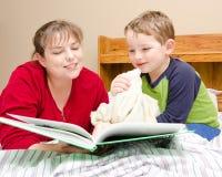 Modern läser läggdagsberättelse till den unga pojken Arkivfoto