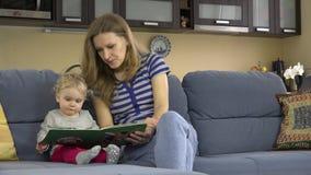 Modern läste boken med lite behandla som ett barn dottern på soffan i rum 4K arkivfilmer
