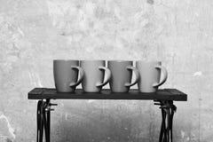 Modern låg tabell med fyra lock av te eller kaffe nära väggen Slags tvåsittssoffahem och cookwarebegrepp Tabell med färgglade kop Arkivbild
