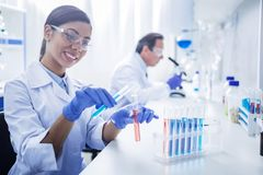 Joyful positive woman working with chemical reagents. Modern lab. Joyful positive smart women sitting at the table and wearing protective glasses while working royalty free stock photos