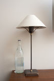 Modern lamp and bottle of water Royalty Free Stock Photography