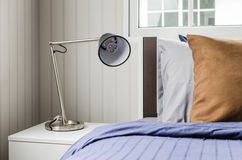 Modern lamp on white nightstand in single bedroom Stock Images