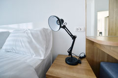 Modern lamp on wooden nightstand in white modern bedroom, interi Stock Photography