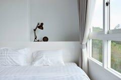Modern lamp on wooden nightstand in white modern bedroom, interi Royalty Free Stock Image