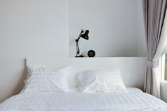 Modern lamp on wooden nightstand in white modern bedroom, interi Royalty Free Stock Photo