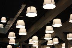 Modern lamps and bulbs hanging from the ceiling radiate light in an office. ceiling of the central library of rotterdam. stock photos