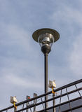 Modern lantern pole with the small lamp. Royalty Free Stock Image