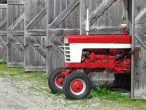 Modern lantgårdtraktor i ett gammalt skjul Royaltyfri Foto