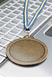 Modern laptop and award a gold medal for success. Stock Photography