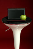 Modern laptop on a chair with green apple Royalty Free Stock Image