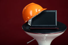 Modern laptop on a chair with helmet Stock Photo