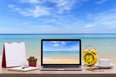 Modern laptop computer, Coffee cup, alarm clock, notebook and ca. Lendar on wooden table and view of tropical beach background. Saved with clipping path. Work stock photos