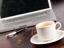 Modern laptop with a cup of coffee Stock Images