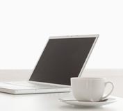 Modern laptop and cup of tea on a table Stock Images