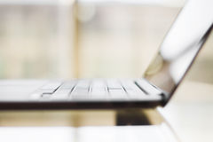 Modern laptop on a glass table, shallow depth of field Stock Photo