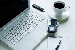 Laptop and Coffee Cup. Modern laptop with mobile phone, cup of coffee, notepad, fountain pen and usb pendrive Stock Photos