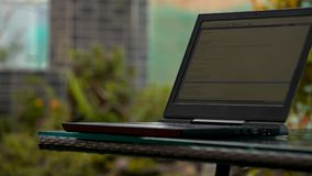 Modern laptop on table against soft focused space. Closeup modern laptop on black table with glass surface against walking past guy and soft focused background stock video footage
