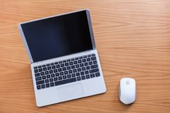 Laptop with mouse over wood table stock photo