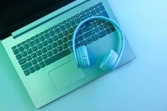 Modern laptop, wireless headphones. Gadgets. Neon night light, ultraviolet. Top view, minimalism. Modern laptop, wireless headphones. Gadgets. Neon night light royalty free stock photo