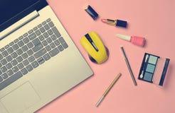 Modern laptop, wireless mouse, cosmetics on a pink pastel backgr stock photo