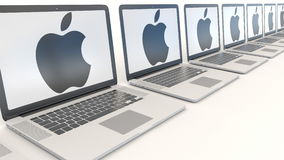 Modern laptops with Apple Inc. logo. Modern office building entrance. Computer technology conceptual editorial 3D.  Stock Photos